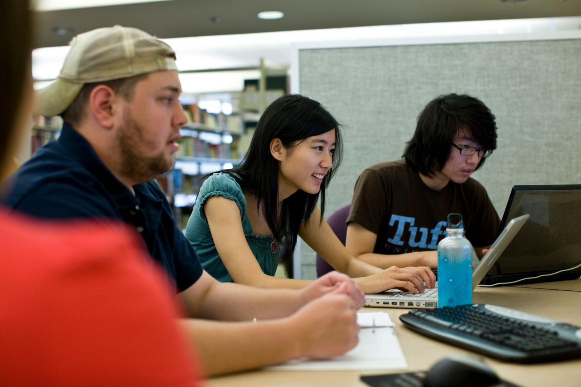 Tufts students working on laptops in Tisch Library